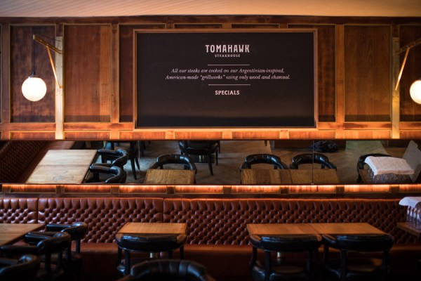 The Tomahawk steakhouse menu board with seats in front of it