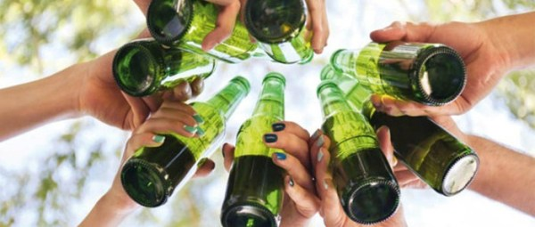 Hands cheering holding bottles of beers. Reducing drinking is a good step to look after your mental health
