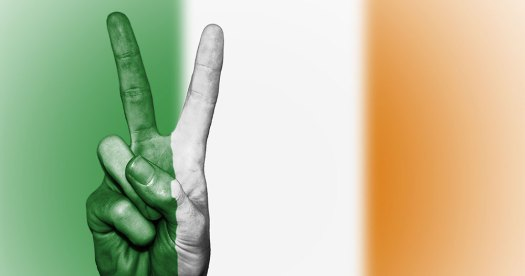A person's hand doing the peace symbol in front of the irish flag for the dublin Human Rights Festival this weekend