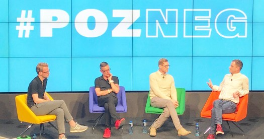 The panellists sitting on colorful chairs at the Pozneg event with screens behind them