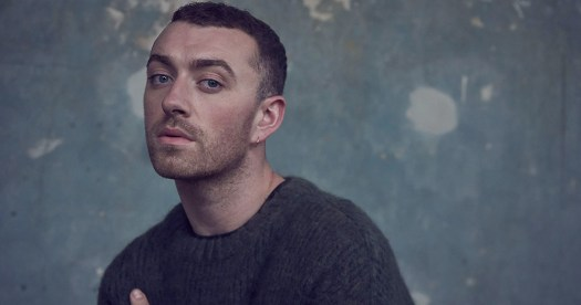 Sam smith standing in front of a splotchy wall