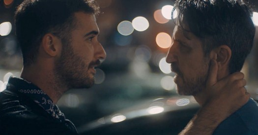 A still from the film call your father with two men looking at each other intensely at night with lights in the background