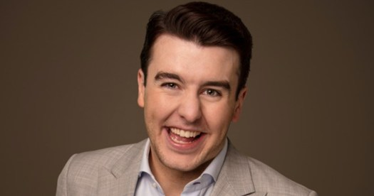 Al Porter smiling in a beige suit against a brown background, the same comedian against which claims of sexual misconduct have emerged