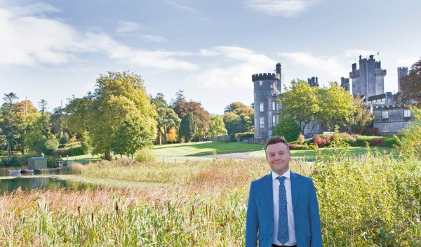 Daragh Doyle, the wedding planner from Rainbow Weddings, standing in front of a stone castle, trees, reeds and a lake