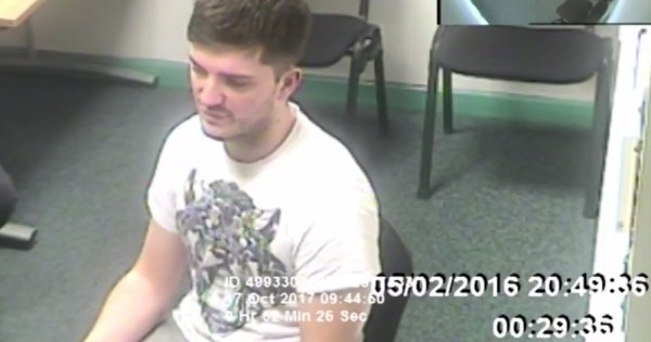 Police footage of Daryll Rowe, the man convicted of intentionally infecting partners with HIV, sitting in a chair in a white tee shirt
