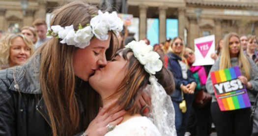 Two women in wedding dresses kiss with marriage equality posters in background