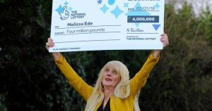 Milissa joyfully holds oversized cheque for £4 million in the air