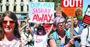 banner reads DUP and Theresa May sashay away