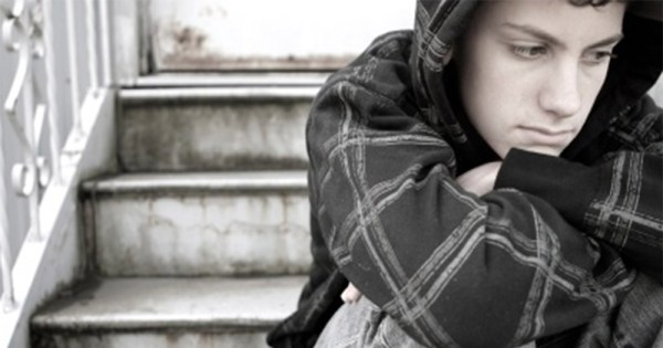 teen suffering from depression sitting on back steps with hood up