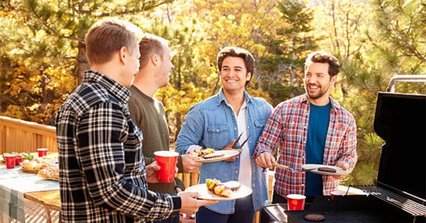 A group of men gathered around a barbecue