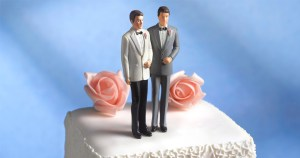 A wedding cake with figurines of a gay male couple on top