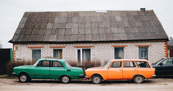 Two ancient looking cars parked bumper to bumper outside a small house in a Russian village