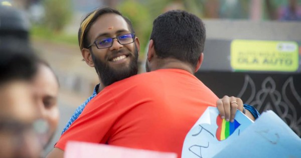 Image of two men hugging in India.