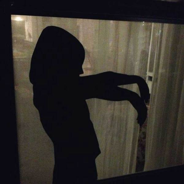 A creepy silhouette glued to the window used as decoration for a Halloween party