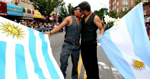 Two men kissing holding Argentina's flag,