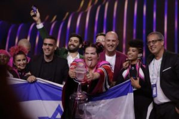 The Israel Eurovision team hold up their flag and trophy