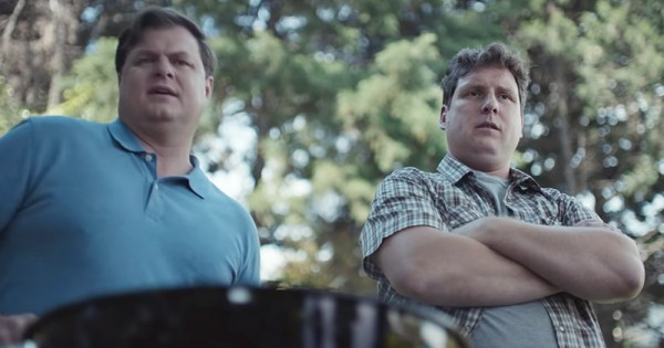 Still from new Gillette ad showing two men at a barbecue, one in a blue shirt and one in a checkered shirt with his arms crossed