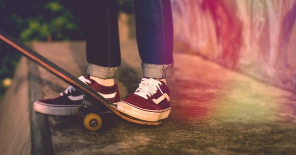 Skateboarders stock image of person's shoes at the foot of a skateboard