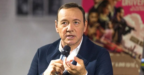 Kevin Spacey holding a microphone.
