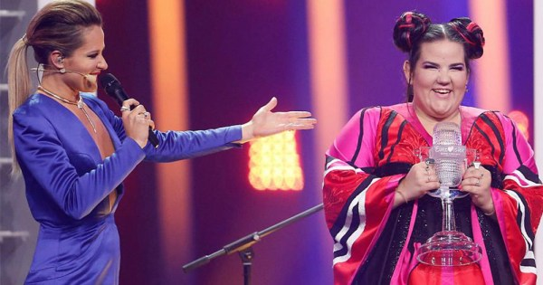 A presenter hands the winner of Eurovision her trophy