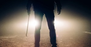 A person holds a weapon in front of a car.