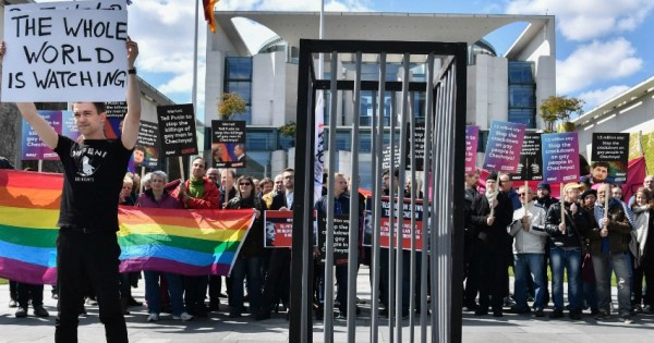 A group of protestors hold signs, rainbow flags in front of a fake prison cell, protesting the purge of LGBT+ people in Chechnya.