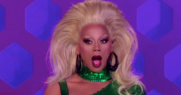 A picture of RuPaul in a blonde wig looking shocked