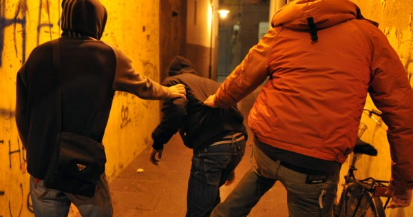 A gang attack a man in an alleyway
