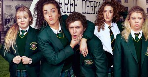 The cast of Derry Girls, four young women and one young man pose comically in front of a Free Derry sign