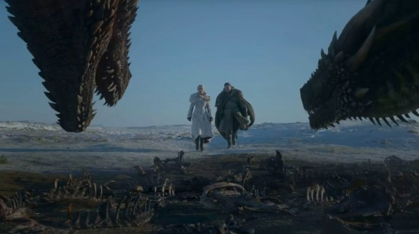 Jon Snow and Daenerys from Game of Thrones shown walking between two dragons