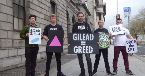 Activists outside the Four courts holding protest signs against pharmaceutical giant Gilead