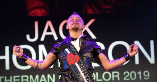 A trans man dressed in leather on stage celebrating winning the competition