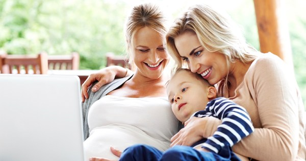 A family with two mothers, one pregnant, and their little boy all smiling on the couch looking at a laptop