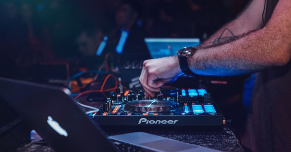 A close up of a DJ in a club using decks