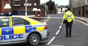 Police Man stands beside police car in Northern Ireland