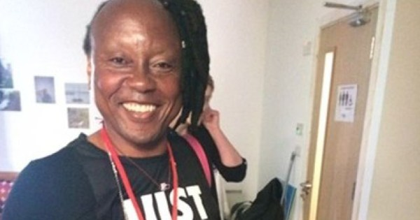 Sylva Tukula, her hair pulled to the side in dreads, smiles at the camera