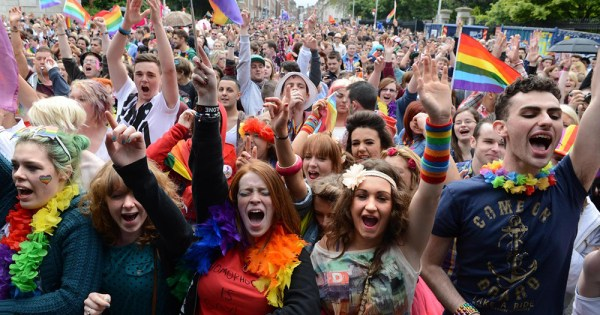 Revellers at Pride in city centre cheer while decked out in rainbow regalia