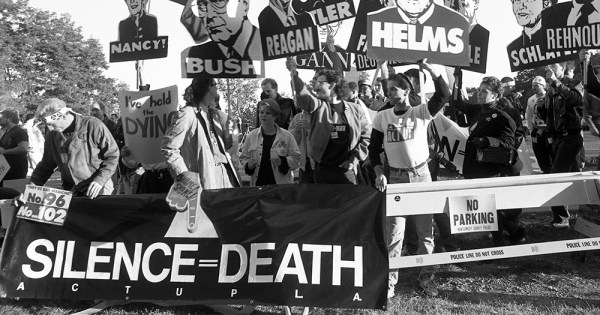 ACT UP hold signs with US government officials images during a HIV/AIDS protest in the 1980s