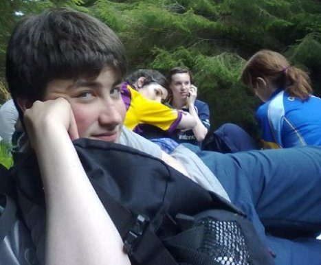 A teenager in rural Ireland lying back on his elbow looking at the camera, a group of young people in the background.
