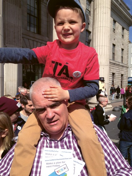 Noel Whelan with his young son on his shoulders standing on O'Connell Street