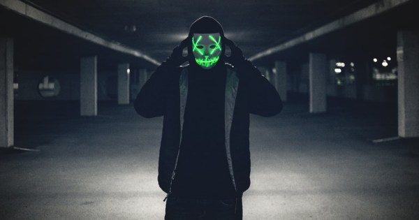 A person wearing Saw like a neon mask in an underground parking lot.