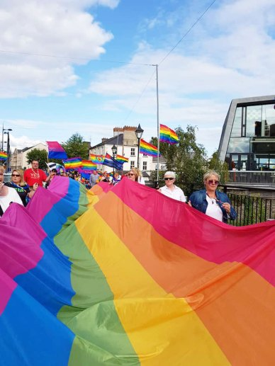 A group of women carry a massive Pride flag through Thurles