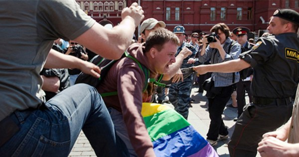 Man holding rainbow flag falling forward as Russia police looks ready to attack.
