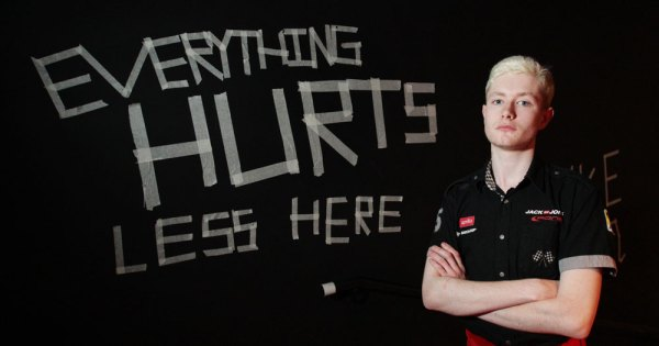 """person from National Youth Theatre stands in front of sign reading """"everything hurts less here"""""""