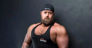 Ireland's first openly gay strongman Chris McNaghten wearing a tank top and a cap.
