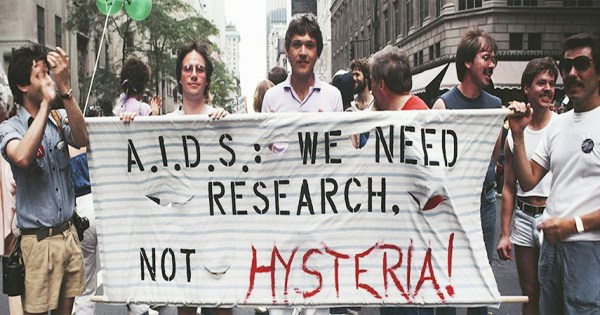 "Activists in New York in the 1980s hold a banner reading ""AIDS we need research not hysteria"""