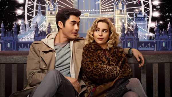 Stars of upcoming festive film Last Christmas Emilia Clarke and Henry Golding sitting on a bench in front of a winter London scene