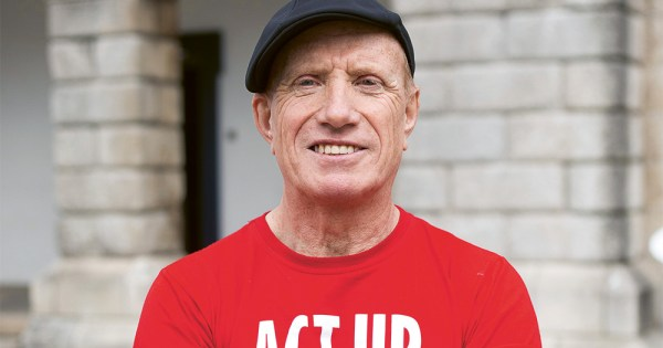 Close up of ACT UP Cork activist Will Kennedy wearing a red t-shirt and a hat