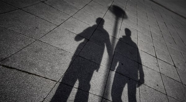 prosecutions the shadows of two men holding hands
