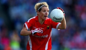 Valerie Mulcahy is wearing a Cork jersey and running with a football mid-game. She has an eager expression.